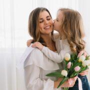 Madre sostiene hija sobre sus brazos besandole