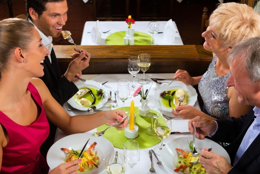 familia cenando junto padres mayores bien vestidos