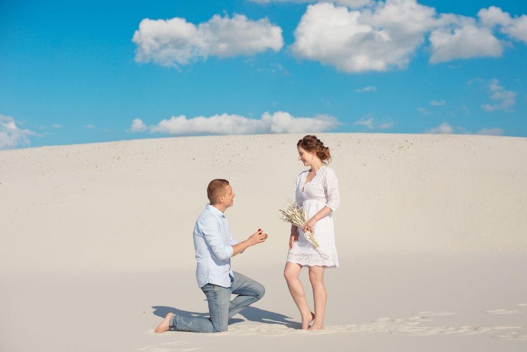 chico arrodillado ofreciendo anillo de compromiso a su novia