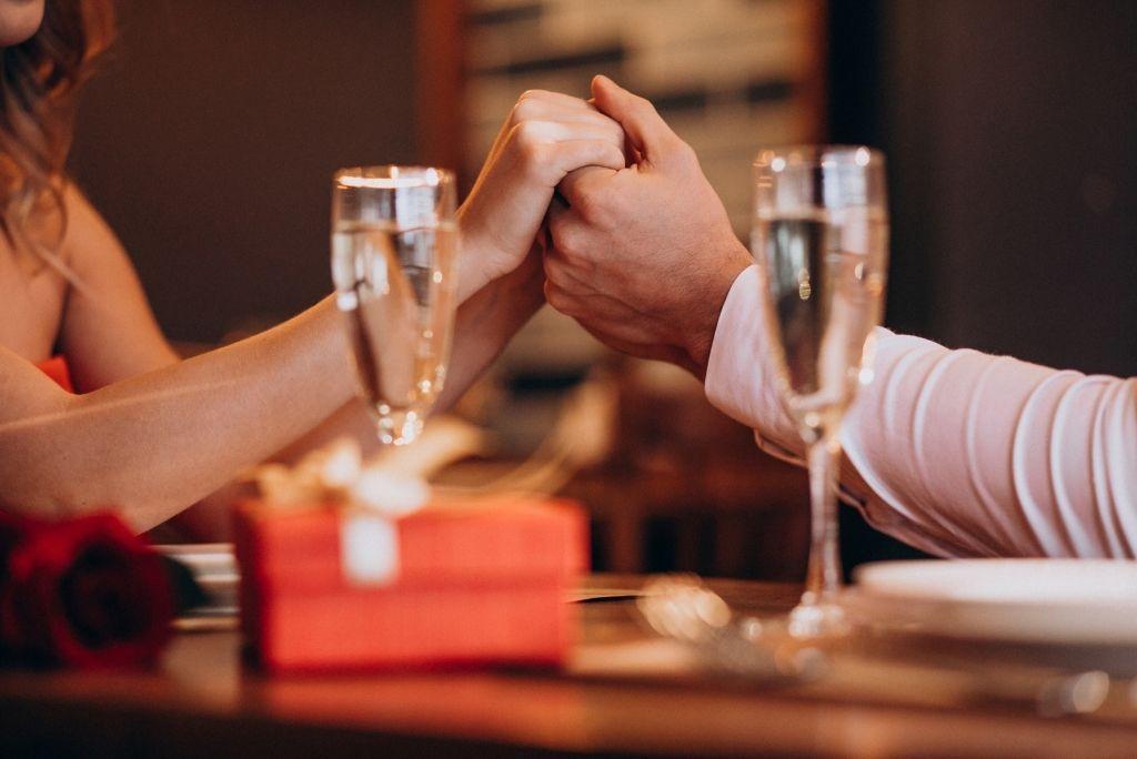 pareja en cena romantica unen sus manos