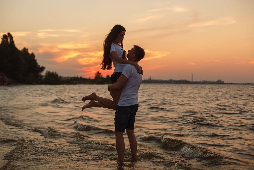 pareja joven abrazados en la orilla de la playa