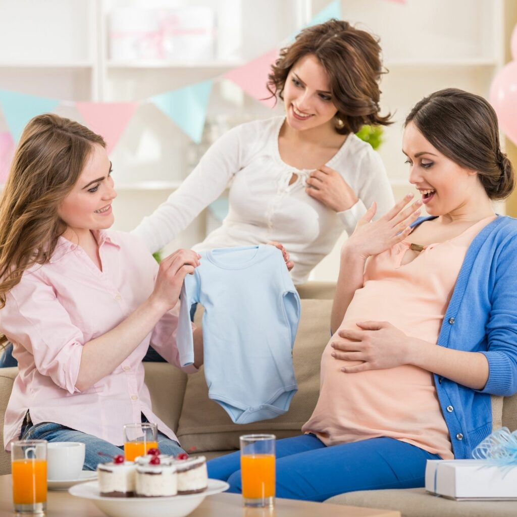 mujer embarazada abre un regalo en la fiesta baby shower