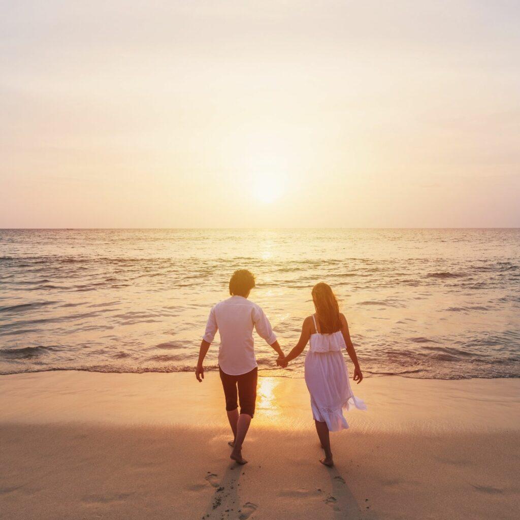 una pareja de enamorados pasean de la mano por la playa
